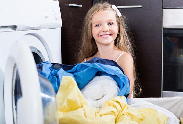 Девочка загружает вещи в стиральную машину