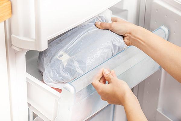 Женщина кладет одежду в пакете в холодильник