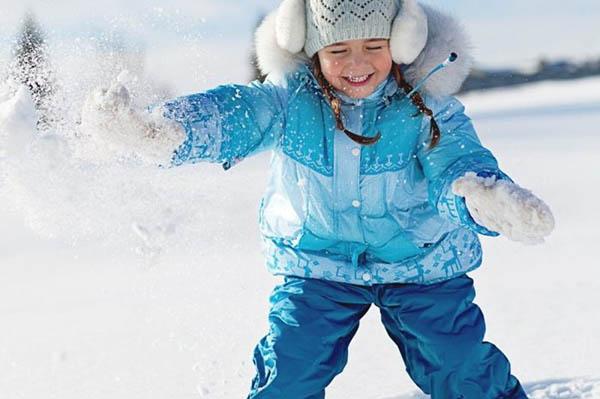 Девочка в зимней одежде играет в снегу