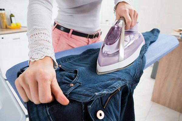 Девушка гладит джинсы
