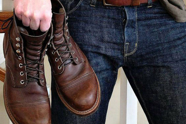 Мужчина держит в руках коричневые ботинки