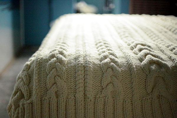 Вязаный акриловый плед на кровати